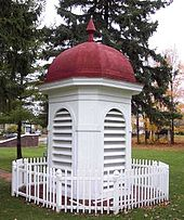 the red-roofed white cupola from the 1927 building, surrounded by a small white picket fence