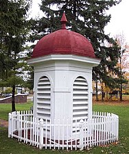 Red-roofed white cupola from the 1927 building, surrounded by a small white picket fence