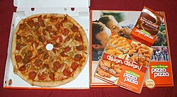North American take-away pizza, from Canadian chain Pizza Pizza. A thick-crust pizza topped with chicken, pepperoni, and italiano blend; also a box of chicken tenders, a bag of two-bite brownies, and another pizza box.