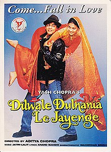 "The Dilwale Dulhania Le Jayenge theatrical release poster shows a man in a black leather jacket and blue jeans holding over his shoulders a woman in a red wedding dress. A caption on top reads ""Come... Fall in Love""."