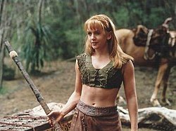 A young blonde woman wearing a green woven tank-top and leather skirt. She holds a wooden fighting staff, a horse can be seen in the background.