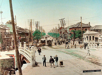 Toyohara Kunichika - Attributed to Adolfo Farsari (1841–1898): A handcolored albumen photograph of Kyobashi as it looked in the 19th century.