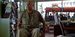 A bald man in a wheelchair, inside a travel agency.