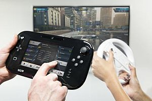 "Need for Speed: Most Wanted (2012 video game) - The Wii U-exclusive cooperative ""Co-Driver"" mode in action. One player drives with the Wii Remote (pictured with the Wii Wheel) while the other provides assistance using the Wii U GamePad."
