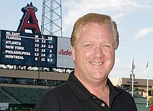 A man is smiling at the camera with the backdrop consisting of the interior of a baseball stadium with the scoreboard displayed prominently.