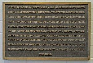 "George Stibitz - This bronze plaque is located in the entryway of McNutt Hall at Dartmouth College reads, ""In this building on September 9, 1940, George Robert Stibitz, then a mathematician with bell telephone laboratories, first demonstrated the remote operation of an electrical digital computer. Stibitz, who conceived the electrical digital computer in 1937 at Bell Labs, described his invention of the ""complex number calculator"" at a meeting of the Mathematical Association of America held here. Members of the audience transmitted problems to the computer at Bell Labs in New York City, and in seconds received solutions transmitted from the computer to a teletypewriter in this hall."""