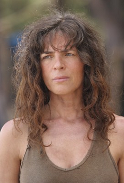 Head and shoulders of an attractive middle aged woman with long curly brown hair, wearing a brown tank top, with a sad frown on her face.