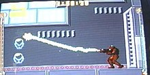 A video game screenshot of a person in a powered exoskeleton firing a beam.