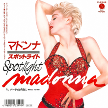 Madonna with short blond hair puts her right hand above her head and looks back. She wears a red dress.