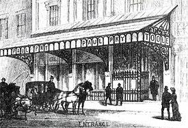 Street view of front of Victorian theatre of modest proportions, with glass and iron canopy across its width