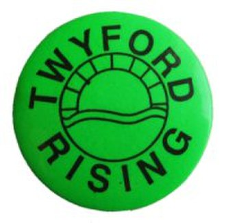 "Twyford Down - ""Twyford Rising"": A button badge worn by supporters of the Twyford Down road protest. Stencil-painted, graffiti versions of this logo appeared around Winchester during the early 1990s."