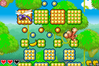 DK King of Swing - Donkey Kong swings on an orange peg as an enemy flies by on the Tropical Treetops level.