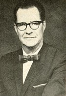 A Caucasian male with glasses wearing a black jacket and white shirt with a bowtie