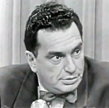 A man sits in front of a microphone looking off to the right. In the background is a curtain and he appears to be in mid conversation.