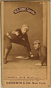 A picture depicting a baseball player who is holding a ball that tagging out another baseball player who attempting to reach base