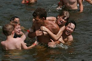 Kids playing in a lake at a church camp