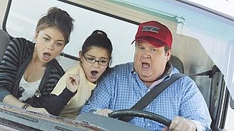 After the Fire (Modern Family) - Cam (Eric Stonestreet) tries to drive a huge moving truck to prove Haley (Sarah Hyland) and Alex (Ariel Winter) that gays can drive trucks