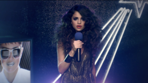 Love You like a Love Song - Gomez in the music video, singing at a Japanese karaoke bar, while the karaoke machine projects her as Max Headroom.