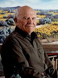 A man of around 90 sits in front of a landscape painting of desert wildflowers