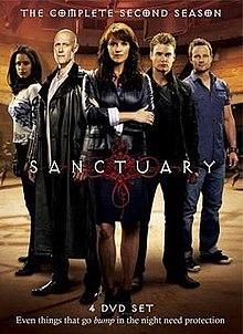"A DVD boxset cover consisting of five people standing behind a logo saying ""Sanctuary"". In the front is a middle-aged brunette woman wearing a black leather jacket and she is crossing her arms. To her right is a bald man with a long black leather overcoat, and a young woman of Indian descent. To the left are two men with short hear, one wearing a black jacket and jeans, the other with a blue shirt and jeans. The background indicates they are inside a large room."