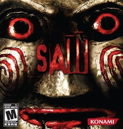 "The box art features the face of an antique-looking Billy doll. The face is gold in color and is shiny. It has red eyes and red lips. The word ""Saw"" in red letters is in the center."