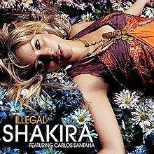 An image showing Shakira laying on flowers looking directly into the camera