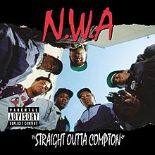The members of N.W.A. look down to the camera and Eazy-E points a gun to it