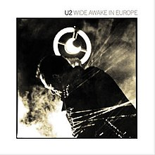"A record sleeve with a sepia-tone photograph of Bono holding a circular-shaped microphone in front of a thick fog. A white border surrounds the image and reads ""U2 Wide Awake in Europe"" at the top right."
