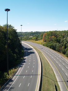An empty six-lane highway in a forested valley