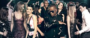 "Bring It (song) - An image of Jodie Connor and Tinchy Stryder dancing in the nightclub scene in the music video for ""Bring It""."