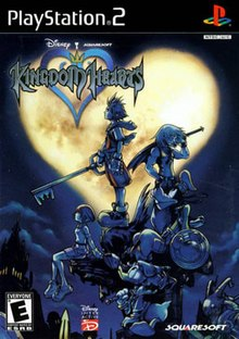"Artwork of a vertical rectangular box. Five people with weapons stand and sit atop a building ledge. A night sky with a heart-shaped moon is in the background. The words ""PlayStation 2"" and ""Kingdom Hearts"" are in the top left corner."