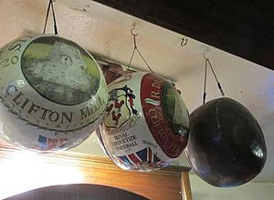 Royal Shrovetide Football - Shrovetide balls typical of those on display in shops and public houses in Ashbourne. These three were on display at the Wheel Inn, Ash Wednesday, 2013. The central ball shows the three cocks that appear on the Cockayne coat of Arms. This image is common to many game balls. To the right is an example of a ball without decoration.