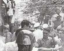 A crowded and narrow street with a lot of people in the vicinity. A tall man with brown hair and sunglasses stands in front of a smaller Asian man with black hair, shielding a shorter man in light shirt with a bloodied face. The smaller Asian man puts an open palm in the air to acknowledge the tall man. A steel-helmeted policeman is in the foreground and others in white caps are in the background.