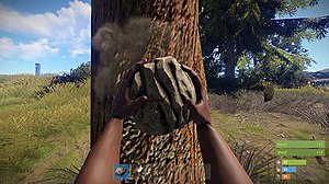 Rust (video game) - The player using the starting rock to gather wood.