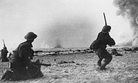 A British soldier fires on German aircraft on Dunkirk's beaches. A bomb blast can be seen in the background