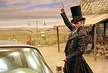 The character Count Olaf, played by Jim Carrey, sports an idyllic top hat and black-striped overcoat, seen from his thighs and up. Behind him shows a bleak cornfield on the left and a gas station on the right. The station has a red-and-white striped awning and looks worn. Olaf faces to the driver's side window of the car, and he positions his right hand as if he's pointing at something above him, while concentrating his eyes on the window and holding car keys in his left hand.