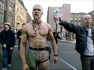 Techno Viking - A man offers an inverted bottle of water to the Techno Viking.