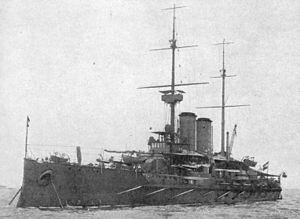 A large battleship at anchor in calm waters with two tall masts and two round funnels.