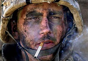 A man with dirt and ash on his face in a military helmet, staring intently forward while he smokes a cigarette