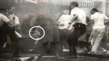 low-resolution monochrome image showing several people in a pub, scattering; one is a policeman. One man, his face circled, sits on the floor in front of the bar, looking bemused.