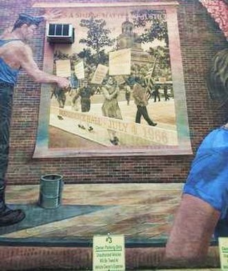 "Barbara Gittings - This is a part of the mural ""Pride and Progress"" by Ann Northrup, located at 1315 Spruce Street, Center City, Philadelphia. In this part of the mural you can see a man pasting up a poster that shows part of the Annual Reminder picket held in 1966. In the poster, the woman with the sign saying SUPPORT HOMOSEXUAL CIVIL RIGHTS is Barbara Gittings."