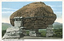 and old postcard of a boulder with a band around it on three small piers of smaller rocks.