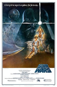 "Film poster showing a man triumphantly holding a laser sword in the air, a woman sitting beside him, and two robots staring at them. A figure of the head of a helmeted man and a space station with several starships heading towards it are shown in the background. Atop the image is the text ""A long time ago in a galaxy far, far away..."" Below is shown the film's logo, above the credits and the release details."
