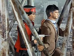 An agent dressed in a scarlet uniform and cap holds a suited civilian man hostage, positioning himself behind the other man so as to shield himself while pointing a gun at an unseen, off-screen enemy. The agent and hostage are standing on a metal structure of girders and supports, which is indicated to be high above ground level by the scale of the streets and buildings below them.