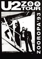 "A black poster with a black-and-white image occupying most it. The image shows U2 walking up the stairs of a small aeroplane as Bono gives a peace sign towards the viewer. Text on the poster reads ""U2 Zoo TV Tour"" and ""Zooropa '93""."