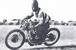 Motorcycle speedway - Col Stewart races his speedway motorcycle wearing a leather helmet. Photo taken around 1930.