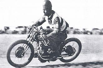 Motorcycle speedway - Col Stewart races his speedway motorcycle wearing a leather helmet. Photo taken around 1930.
