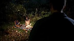 A woman is sitting on blanket with picnic materials around her. The scene is dimly lit, and a dark figure approaches.