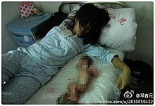 A woman lies on a bed, staring blankly; next to her is a bloody baby that is partially obscured by computerized blurring