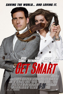 Maxwell Smart, wearing suit and holding a gun, his tie blown to the side, covering the face of Agent 99 who is standing behind him wearing a white jacket.